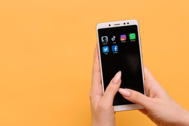 메인 로고 앱 clubhouse, tik tok, instagram, facebook, whatsapp 및 twitter는 여성의 손에 스마트 폰 화면에 표시됩니다.
