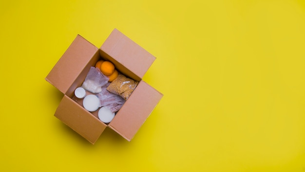 Main products for self-isolation in a box: cereals, buckwheat, fruit, canned food on a yellow background.
