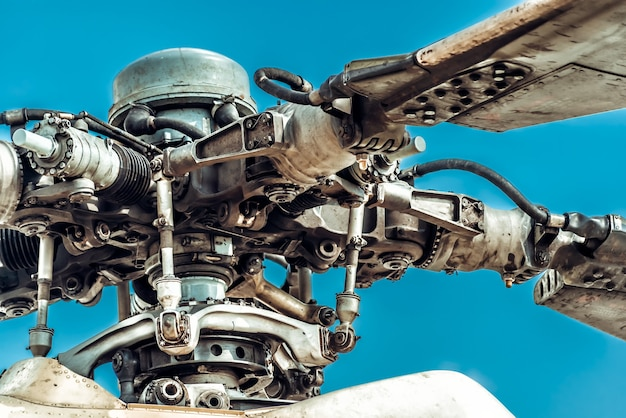 Main rotor blades and rotor head of military helicopter against blue sky