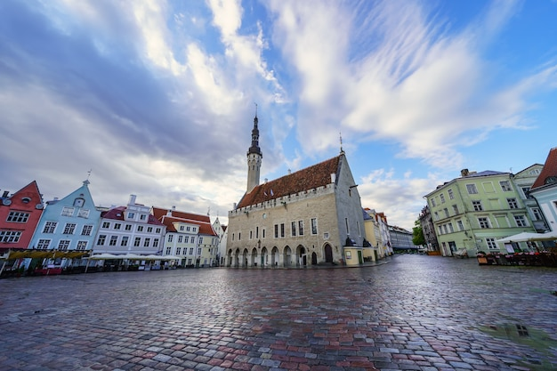 雨が降った後の日の出に中世の建物があるメイン広場。タリンエストニア。