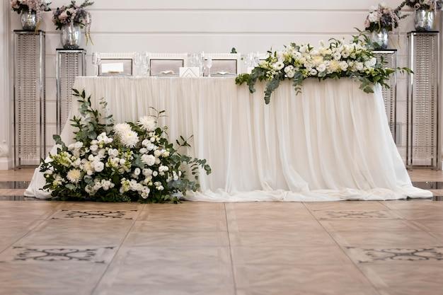 Главный стол на свадебном приеме с красивыми живыми цветами. день свадьбы.