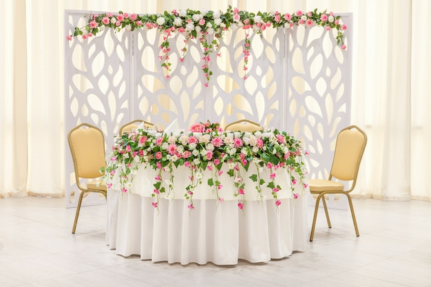 The main table of the newlyweds, decorated with a floral composition and an arch in pastel colors