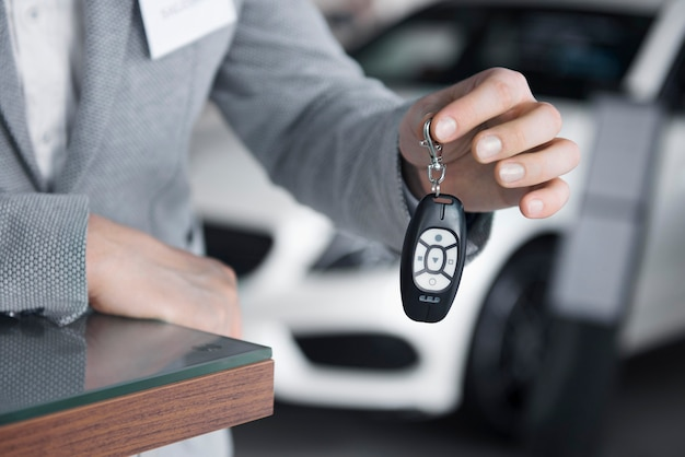 Main view of salesman holding car keys