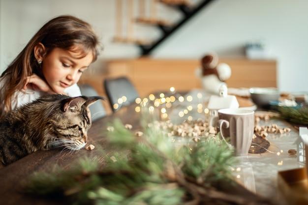 メインクーンの猫とかわいい女の子がクリスマスの装飾の隣のテーブルに座っています。の概念