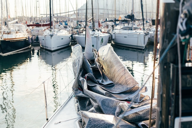 Mainsail or spinnaker put down and folded on deck of professional luxury sailboat or yacht, docked in yard or marina