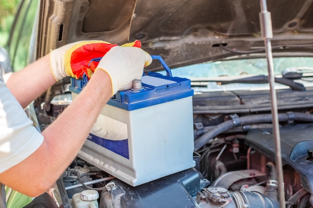 Maintenance of the machine. a male car mechanic takes out a battery from under the hood of a auto to repair, charge or replace it.