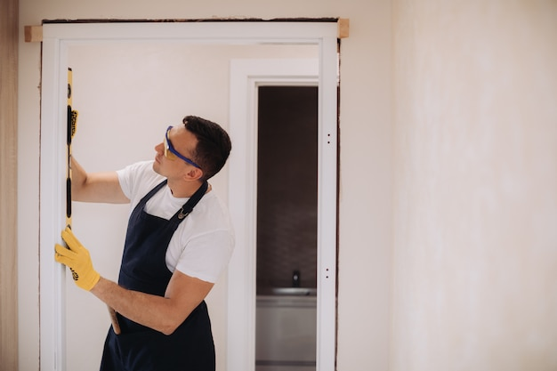 Maintenance man fixing doors with instruments