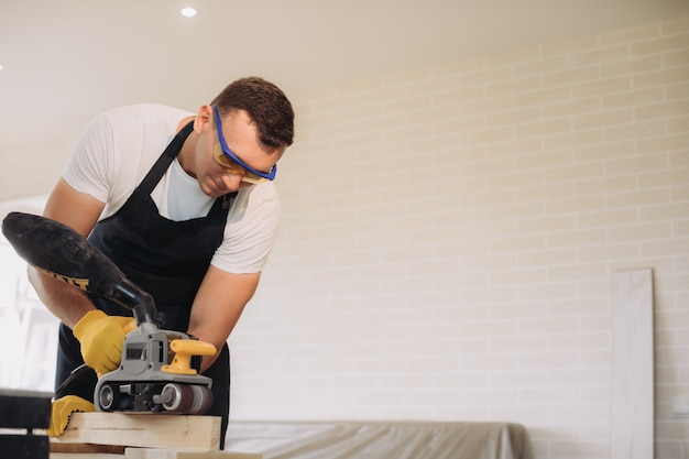 Maintenance man fixing furniture with a special equipment