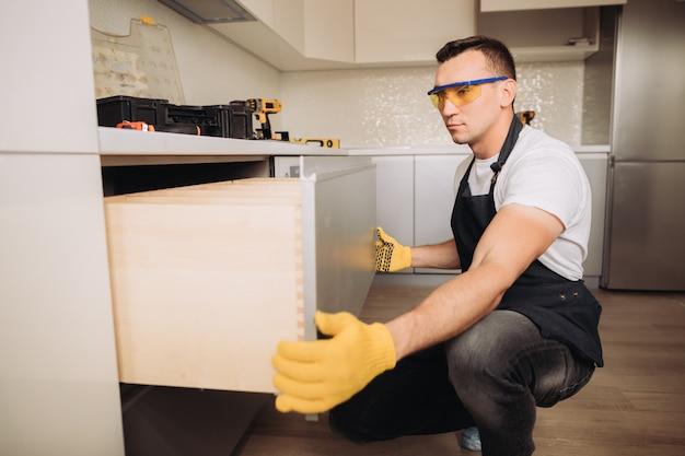 Maintenance man installing kitchen furniture