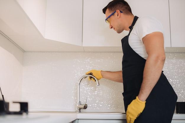 Maintenance man installing plumbing equipment in the kitchen