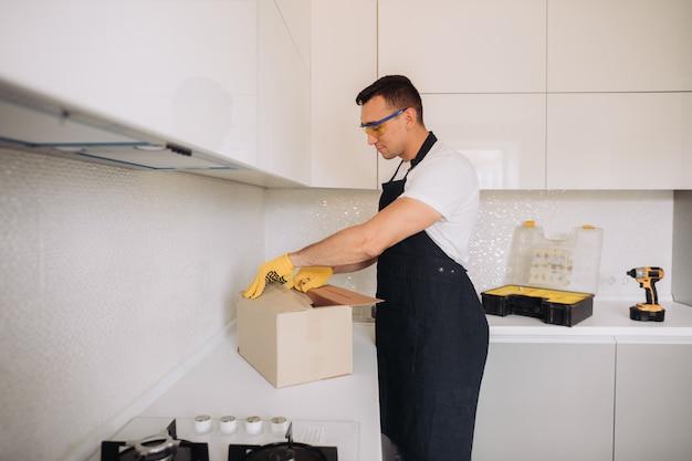 Maintenance man opens the box with plumbing equipment