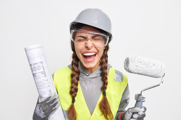 Maintenance and occupation concept. overjoyed female engineer poses with blueprint and paint roller dressed in safety clothes busy reconstructing at construction site isolated over white wall