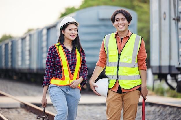 安全スーツを着た保守技術者が、レンチを持った貨物列車の横に立っています。アジアの労働者は鉄道輸送業界で働いています。エンジニアと修理のコンセプト。安全第一