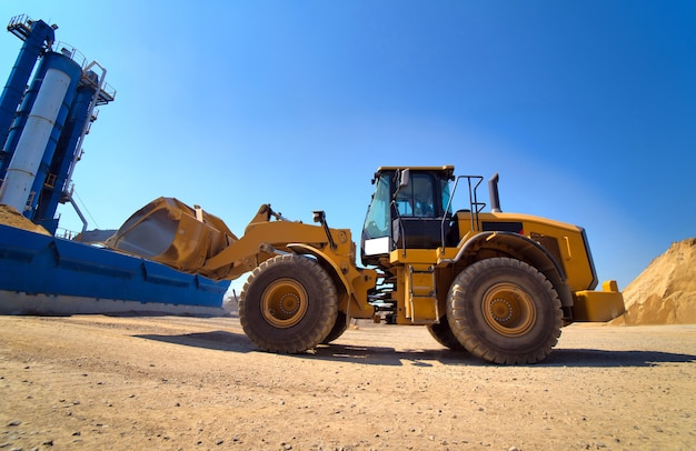 Maintenance of yellow excavator on a construction site against blue sky