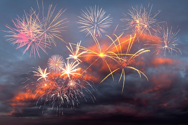 Majestic colorful holiday fireworks in the evening sky with majestic clouds