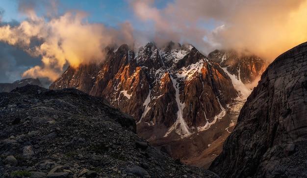 雄大な氷河は、明るい金色の夕陽に照らされています。全景。アルタイ山脈。