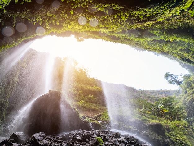 Majestic madakaripura waterfall flowing on rocky cliff