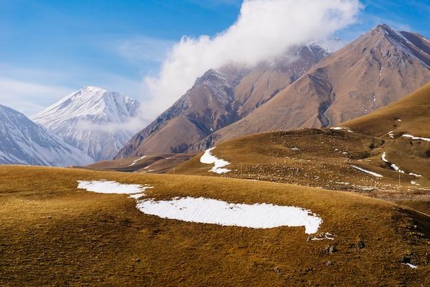 雄大な魔法の自然、白い雪に覆われた高い山々、青い空の下の果てしない黄色い牧草地