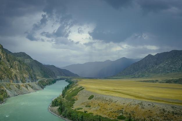 Величественный горный пейзаж в дождливый летний или осенний день. прекрасный вид на излучину реки катунь, равнины и скалы. потоки дождя, пасмурное небо. природные фоны.