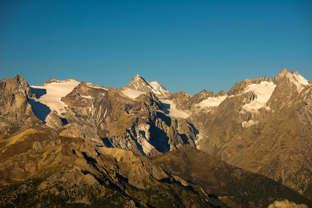 The majestic peaks of the massif des ecrins (4101 m) national park with the glaciers, in france. telephoto view from distant at sunrise. clear sky, autumn colors.