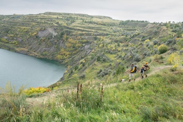 川や湖を囲む広大な山々と現代的なバックパッカーが歩道を移動する秋の自然の雄大な風景
