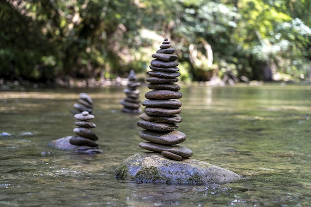 川の水の上でバランスの取れた多くの石のピラミッドの雄大なショット