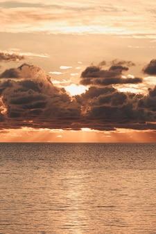 오렌지 톤과 복사 공간에 바다 위로 일몰 동안 구름을 통해 오는 장엄한 태양 플레어