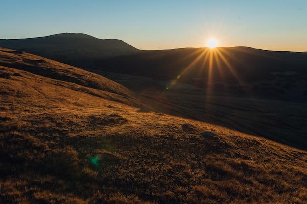 山の風景の中の雄大な日の出。日没時間。カルパチア、ルーマニア、ヨーロッパ。美の世界。