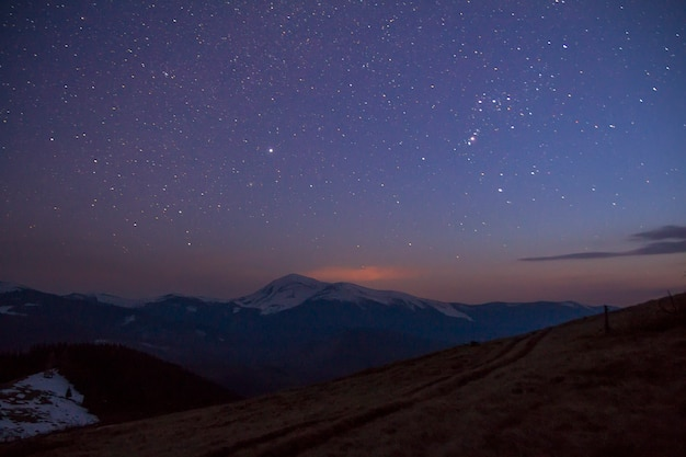 Величественный вид фантастического звездного темного неба над великолепными карпатскими горами, покрытыми вечнозелеными лесами и заснеженными вершинами на расстоянии. захватывающая панорама красоты и волшебства природы.