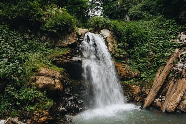 Величественный водопад в горах россии.