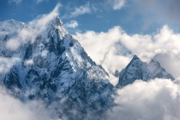 Majestical scene with mountains with snowy peaks in clouds in nepal
