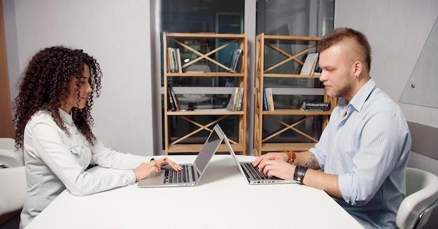 사무실에서 노트북을 사용하여 책상에서 일하는 주요 파트너