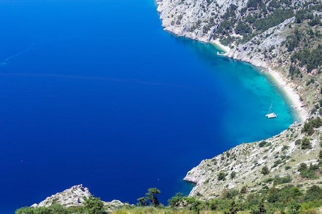 マカルスカリビエラ海岸の夏の景色、ビーチ、紺碧の水面、セーリングヨット(クロアチア)