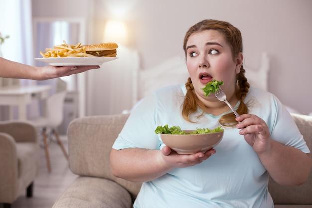 선택하십시오. 건강한 음식과 정크 푸드 사이에서 선택하는 동안 소파에 앉아 통통한 젊은 여성