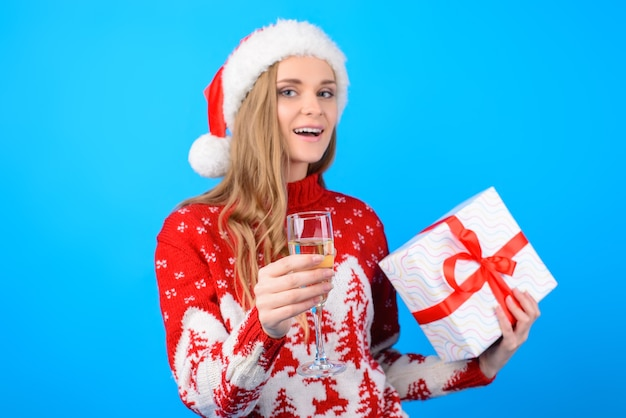 소원을 말해봐! 니트 스웨터에 빨간 산타 모자에 웃는 아름 다운 행복 한 여자의 초상화, 그녀는 토스트를 제기하고 밝은 파란색 배경에 고립 된 선물 상자를 들고
