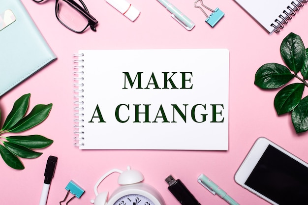Make a change is written in a white notebook on a pink background surrounded by business accessories and green leaves
