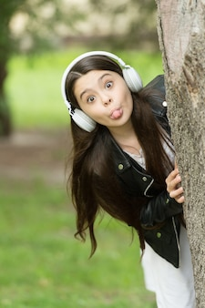 子供時代を遊び心のあるものにします。遊び心のある女の子は木に舌を突き刺します。小さな子供は屋外でしかめっ面。遊び心のあるしかめっ面の赤ちゃん。音楽と楽しさ。新鮮な空気を楽しんでいます。余暇と喜び。遊び心があり、陽気です。