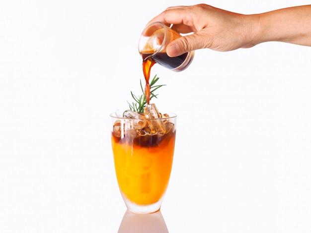 白い壁に分離された氷でオレンジフルーツジュースとカクテル冷たい夏の飲み物を作る。