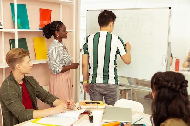 노력하십시오. 그녀의 학생을 듣는 동안 그녀의 얼굴에 미소를 유지 기쁘게 아프리카 계 미국인 여자