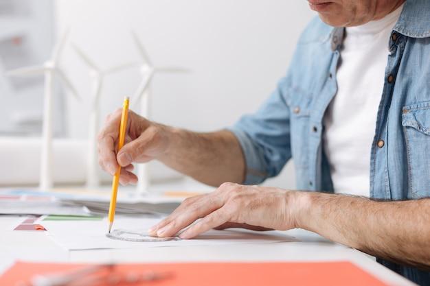 모든 것을 올바르게 만드십시오. 청사진을 그리는 동안 테이블에 앉아 각도기를 사용하는 전문 숙련 된 엔지니어