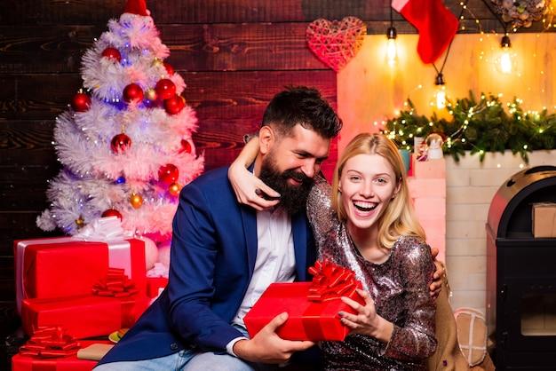재미있는 얼굴을 만드십시오. 크리스마스 트리 조명 배경 위에 패션 커플입니다. 표현과 사람 개념