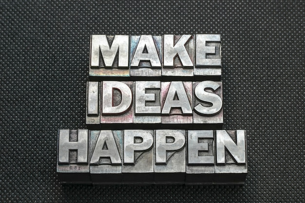 Make ideas happen phrase made from metallic letterpress blocks on black perforated surface