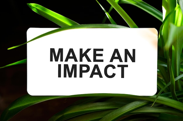 Make an impact text on white surrounded by green leaves