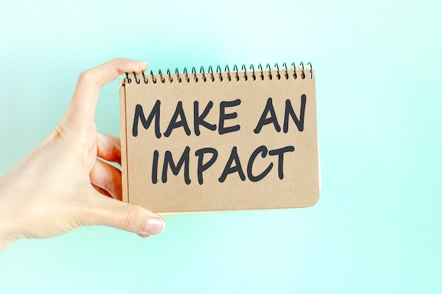 Make an impact word inscription on card paper sheet in hands of a businesswoman. black letters on craft colour paper. business concept