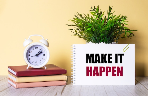 Make it happen is written in a notebook next to a green plant and a white alarm clock, which stands on colorful diaries.