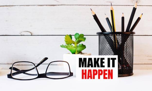 スタンドとメガネの鉛筆の横にある白い名刺に書かれた「makeithappen」。近くには鉢植えがあります。