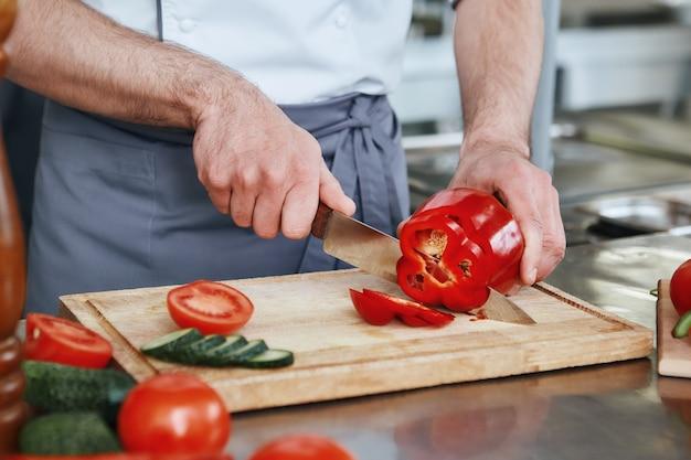Сделайте это своей миссией для шеф-повара по правильному питанию, готовящего блюдо на коммерческой кухне крупным планом