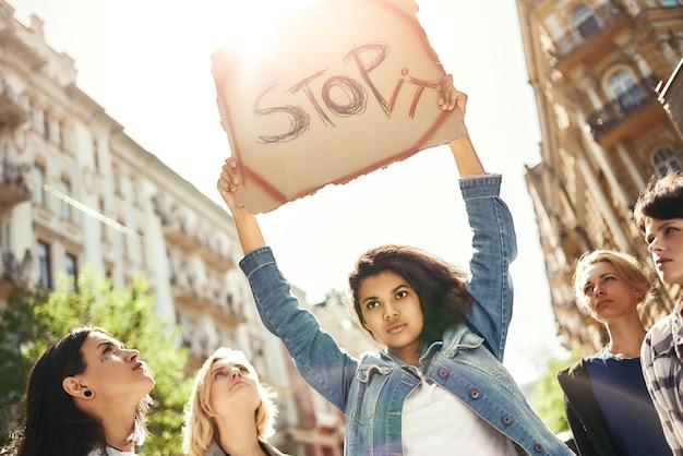 言葉で看板を持っている強い若い女性がそれを止めて戦わないで愛を作る