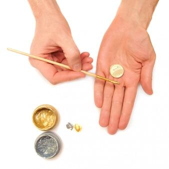 Зарабатывать. концепция. руки, монеты, золотые и серебряные краски на белом