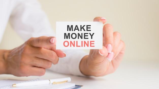 Сделать деньги онлайн слова надписи на листе бумаги белой карты в руках женщины. черные и красные буквы на белой бумаге. бизнес-концепция, серый фон